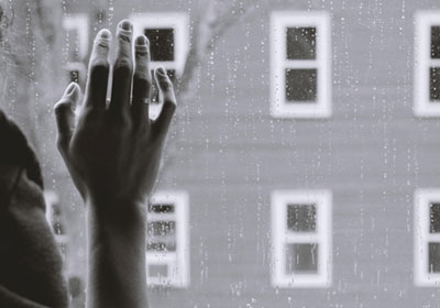 A woman's hand resting against a windowpane suggests grief. In counselling, the dual process model of grief states that both denying and avoiding are important parts of a healthy grieving process.