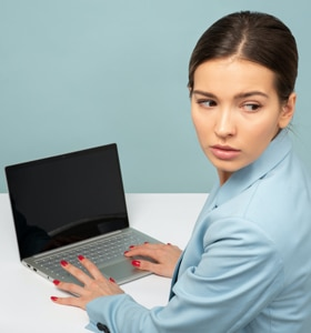 Contracting for Online Therapy - woman in front of her laptop looks over her shoulder to ensure privacy
